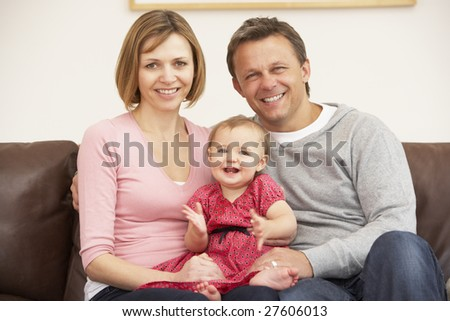 Parents And Baby Daughter On Sofa