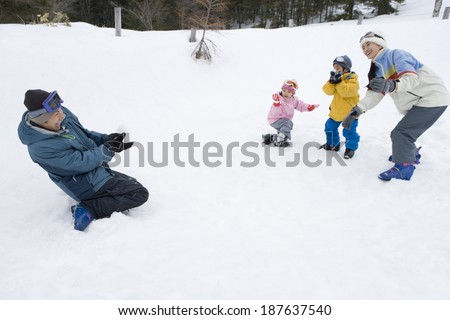 parents and child having snowball fight - stock photo