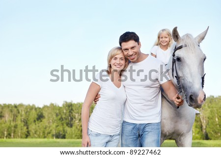 Parents and child with a horse - stock photo