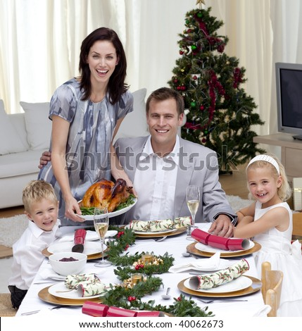 Parents and children celebrating Christmas dinner with turkey at home - stock photo