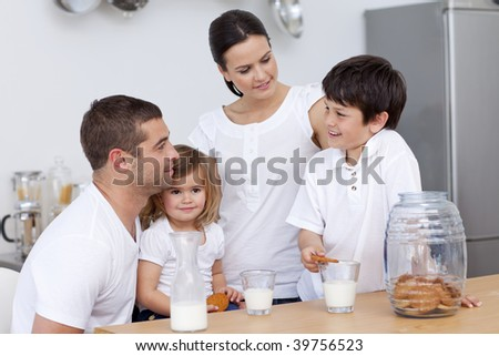 Parents and children eating biscuits and drinking milk in the kitchen