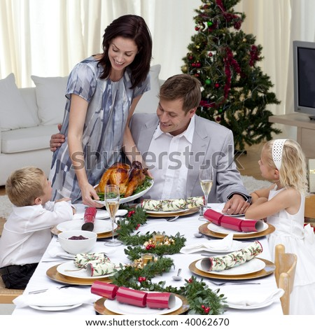 Parents and children in Christmas dinner with turkey at home