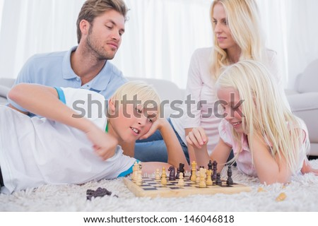 Parents and children playing chess in the living room - stock photo