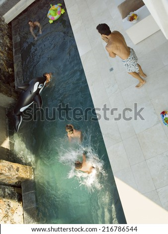 Parents and children playing in the swimming pool. - stock photo