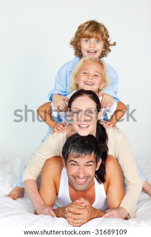 Parents and children playing together in bed - stock photo