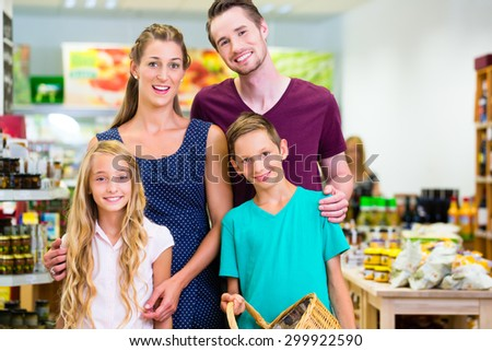 Parents and children selecting vegetables while grocery shopping in organic supermarket  - stock photo