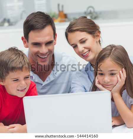Parents and children using a laptop in the kitchen - stock photo