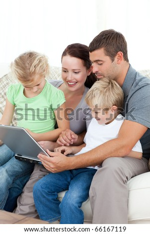 Parents and children using their laptop together sitting on the sofa at home