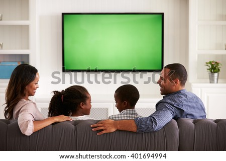 Parents and children watching TV, looking at each other - stock photo