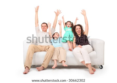 Parents and children with rised hands  on white leather sofa - stock photo