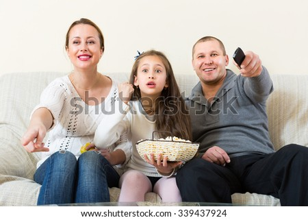 Parents and cute girl watching TV show and smiling indoors. Focus on girl - stock photo