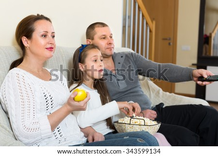 Parents and cute girl watching TV show together and smiling indoors. Focus on woman - stock photo