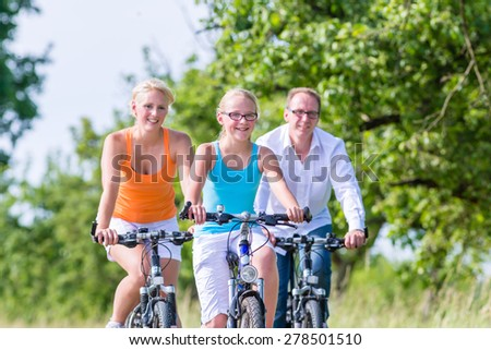 Parents and daughter have bicycle or bike tour on country lane - stock photo