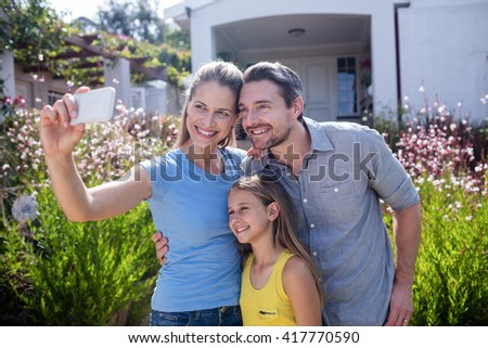 Parents and daughter in garden taking a selfie on mobile phone - stock photo