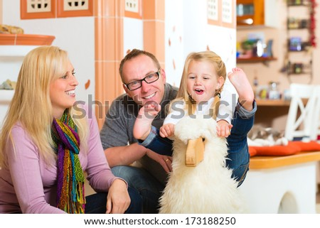 Parents and daughter rocking and playing with rocker horse in living room - stock photo