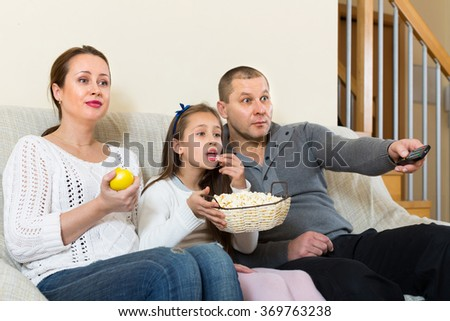 Parents and daughter watching TV show together and smiling indoors. Focus on woman - stock photo