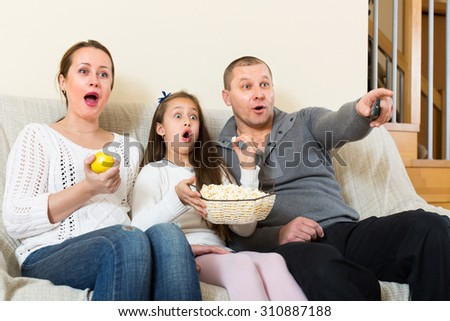 Parents and daughter watching TV show together at home. Focus on  woman - stock photo
