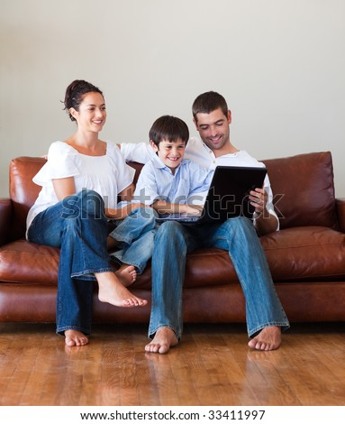 Parents and kid playing with a laptop on a couch at home - stock photo