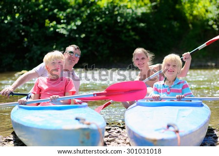 Parents and kids kayaking on the river. Active happy family, father, mother and two teenage school boys, having fun together enjoying adventurous experience on a sunny day during summer vacation. - stock photo
