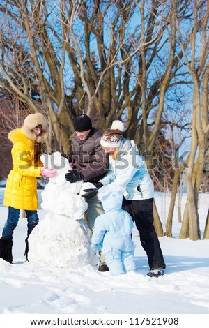 Parents and kids making snowman - stock photo