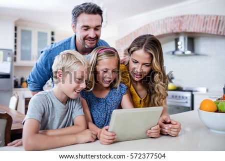 Parents and kids using digital tablet in kitchen at home