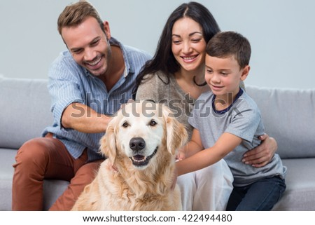 Parents and son petting dog in living room - stock photo