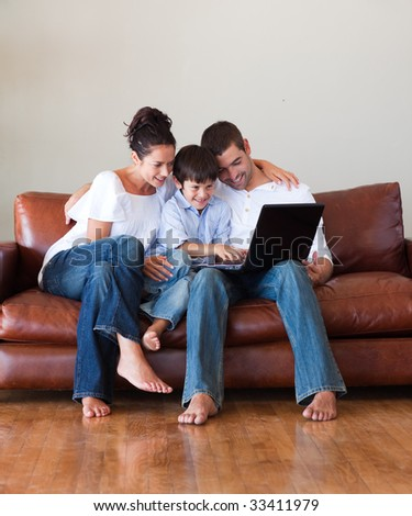 Parents and son playing with a laptop at home - stock photo