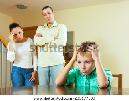 Parents and teen son after quarrel at home. Focus on boy - stock photo