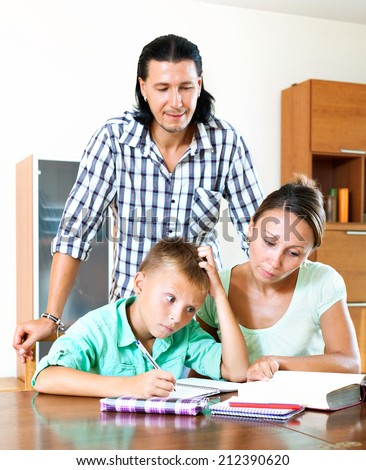 parents and teenager helping with homework in home interior