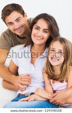 Parents and their daughter smiling on a sofa