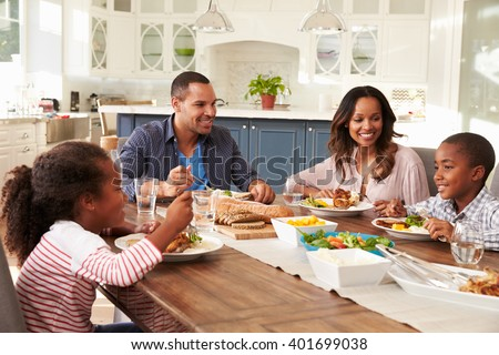 Parents and their two children eating at kitchen table - stock photo