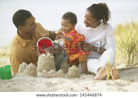 Parents and toddler building sand castle at beach - stock photo