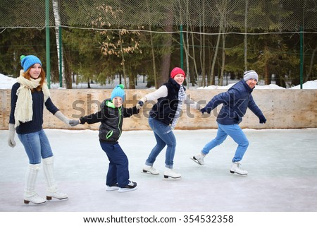 Parents and two children in the skating rink - stock photo