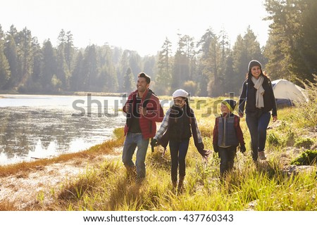Parents and two children walking near a lake, close up