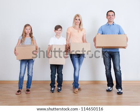 Parents And Two Children With Cardboard Boxes, Indoors