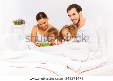 Parents and two kids play with tablet on white bed - stock photo