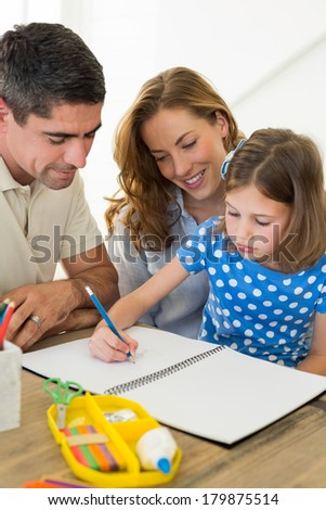Parents assisting daughter in coloring at home - stock photo