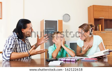Parents berates her underachiever son in home interior - stock photo