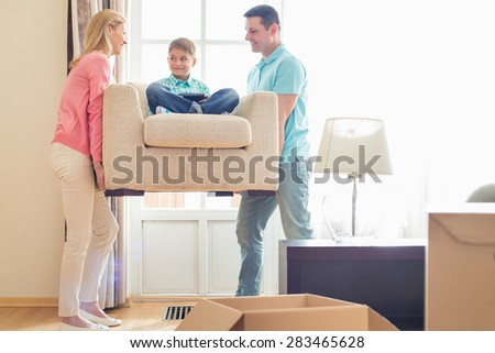 Parents carrying son on armchair in new house - stock photo