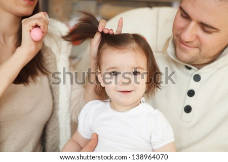 Parents combing they baby's hair - stock photo