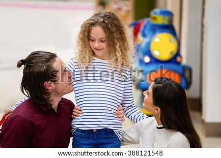 Parents enjoying with their daughter in shopping mall - stock photo