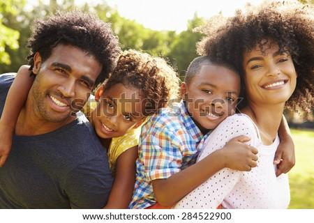 Parents Giving Children Piggyback Ride In Garden - stock photo