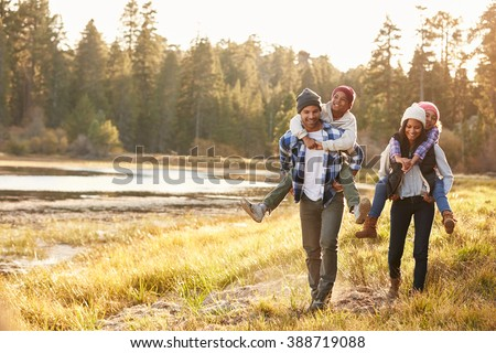 Parents Giving Children Piggyback Ride On Walk By Lake - stock photo