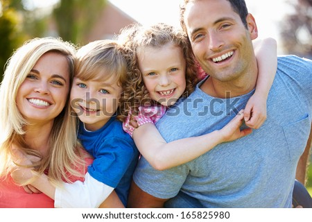 Parents Giving Children Piggyback Rides In Garden - stock photo