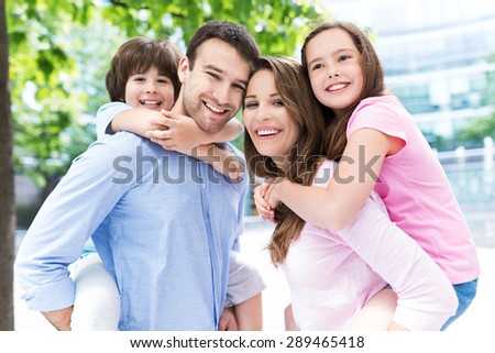 Parents giving kids piggyback ride  - stock photo