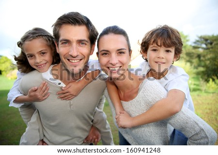 Parents giving piggyback ride to children - stock photo