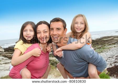 Parents giving piggyback ride to children - stock photo