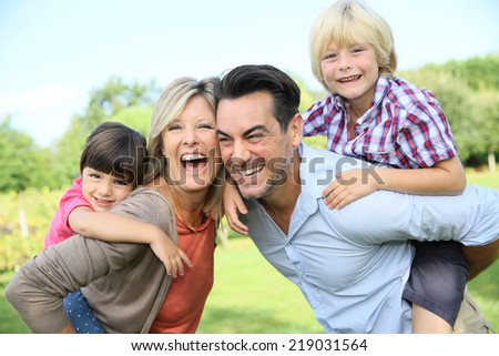 Parents giving piggyback ride to kids in park - stock photo