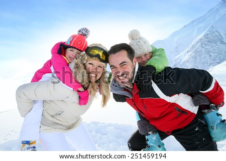 Parents giving piggyback ride to kids in snowy mountains - stock photo
