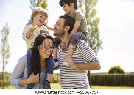 Parents Giving Sons Ride On Shoulders During Walk